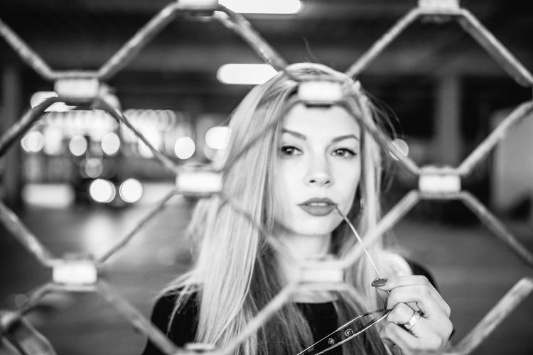 Portrait Of Young Woman Standing At Parking Garage Seen Through Fence
