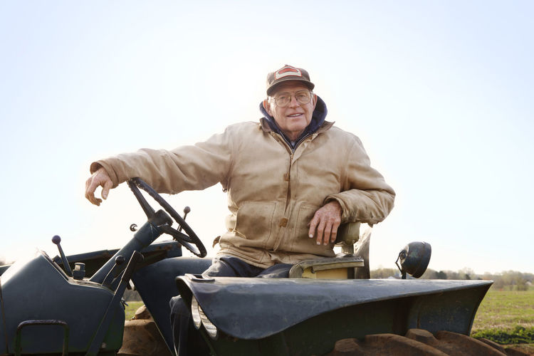 Portrait of confident farmer driving tractor against sky