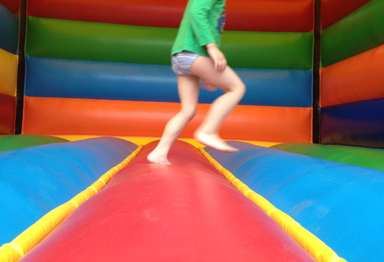 Low Section Of Playful Boy In Inflatable Bouncer