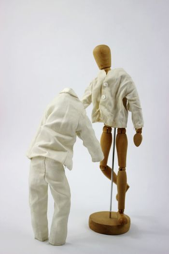 Side view of man with toy standing against white background