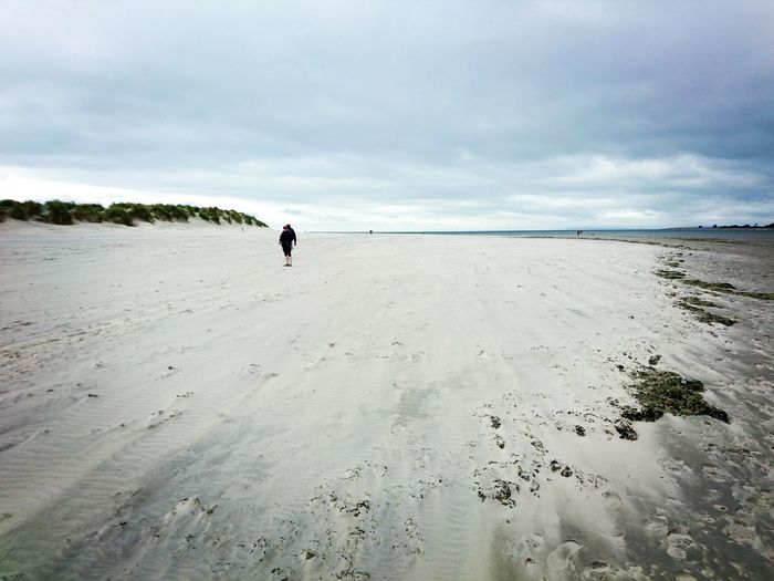 Man and woman standing on sandy beach