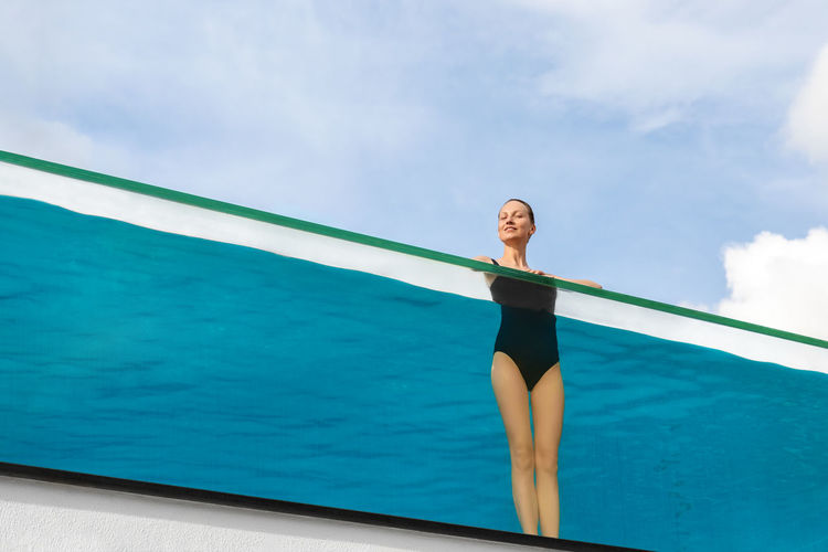Woman standing by swimming pool against sky