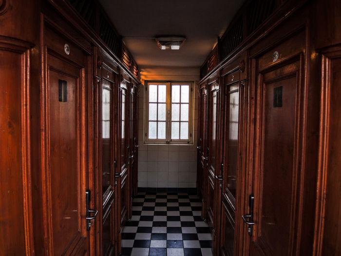 Empty Corridor Amidst Public Restrooms