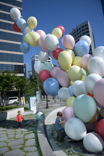 Architecture Balloon Building Building Exterior Built Structure City City Life Day Group Of People Incidental People Leisure Activity Lifestyles Men Multi Colored Nature Outdoors People Real People Sky Street Women