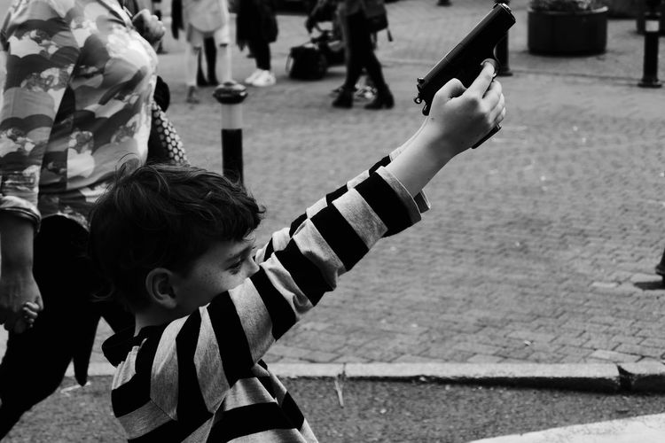 Side view of boy with arms raised holding toy gun on sidewalk