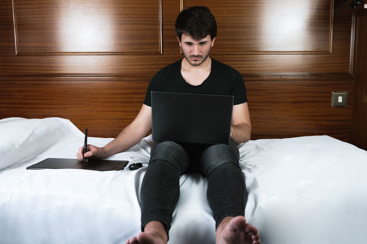 Full length of man using mobile phone while sitting on bed