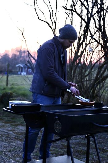 Man standing outdoors by the grill