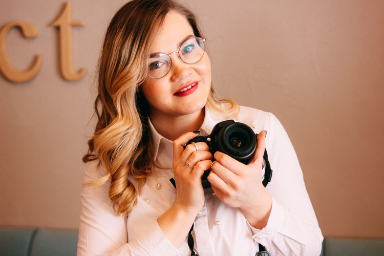 Candid portrait of beautiful blonde girl woman photographer with her camera at work One Person Portrait Young Adult Front View Camera - Photographic Equipment Photography Themes Holding Indoors  Smiling Technology Looking At Camera Young Women Women Hair Eyeglasses  Adult Glasses Beauty Beautiful Woman Hairstyle Photographer