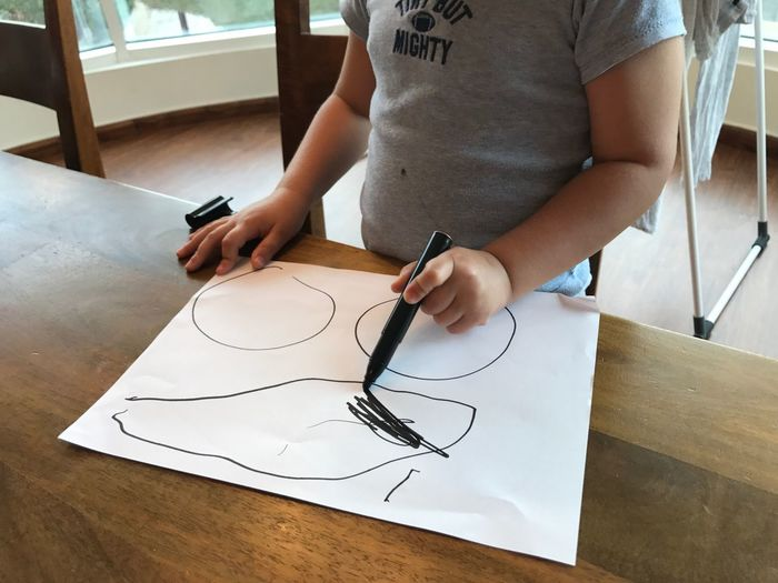 Midsection of boy drawing on paper