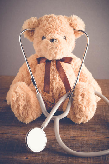Animal Representation Animal Themes Brown Close-up Creativity Cute Healthcare And Medicine Indoors  Mammal Medical Supplies No People Representation Stethoscope  Still Life Stuffed Toy Table Teddy Bear Toy Wood - Material