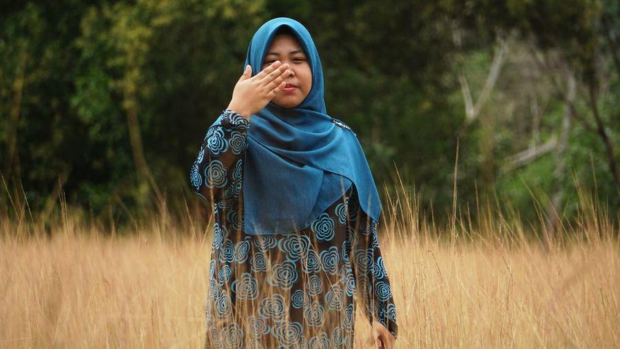 Woman wearing hijab on grassy field