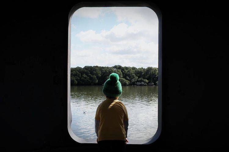 Rear View Of Boy Wearing Knit Hat Sitting In Front Of River