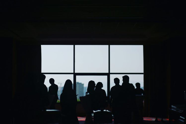 Silhouette people in board room during meeting at office