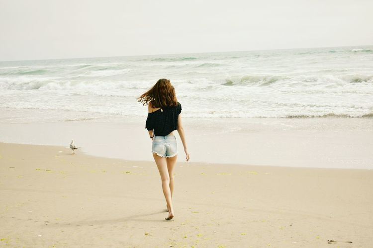 Rear View Of Woman Walking On Beach Against Sky