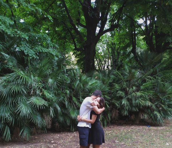 Couple embracing against plants at park