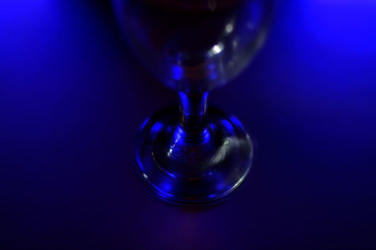 Close-up of bubbles in glass against blue background