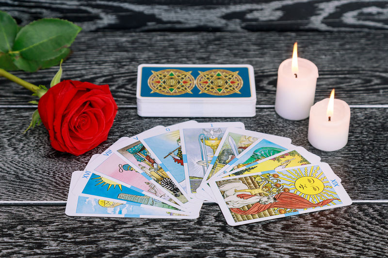 High angle view of tarot cards with candles and rose on table