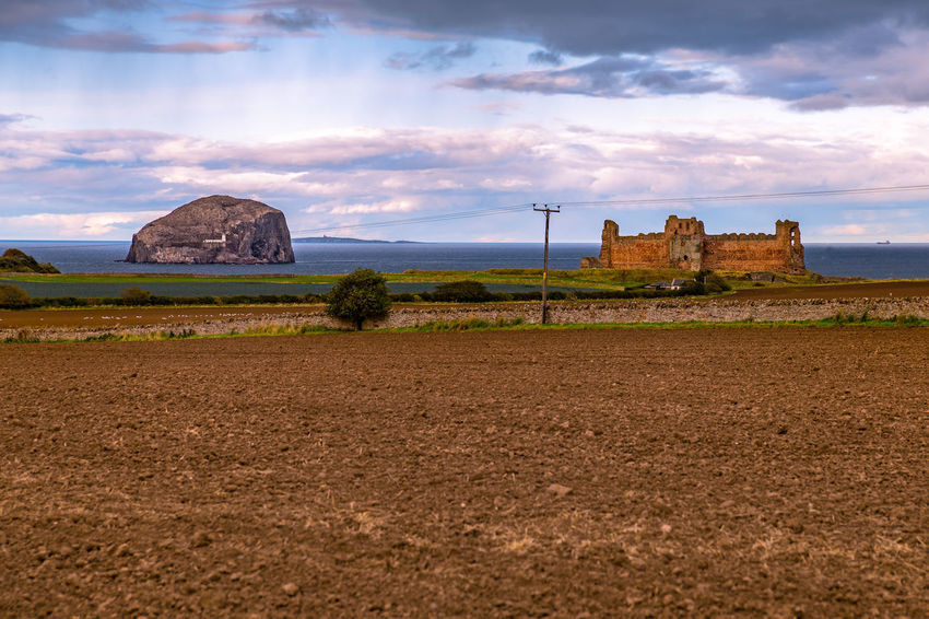 The Bass Rock and Tantallon Castle near North Berwick, United Kingdom. Bass Rock Tantallon Castle Architecture Beauty In Nature Building Exterior Built Structure Cloud - Sky Day History Nature No People Outdoors Sky Tourism Travel Destinations