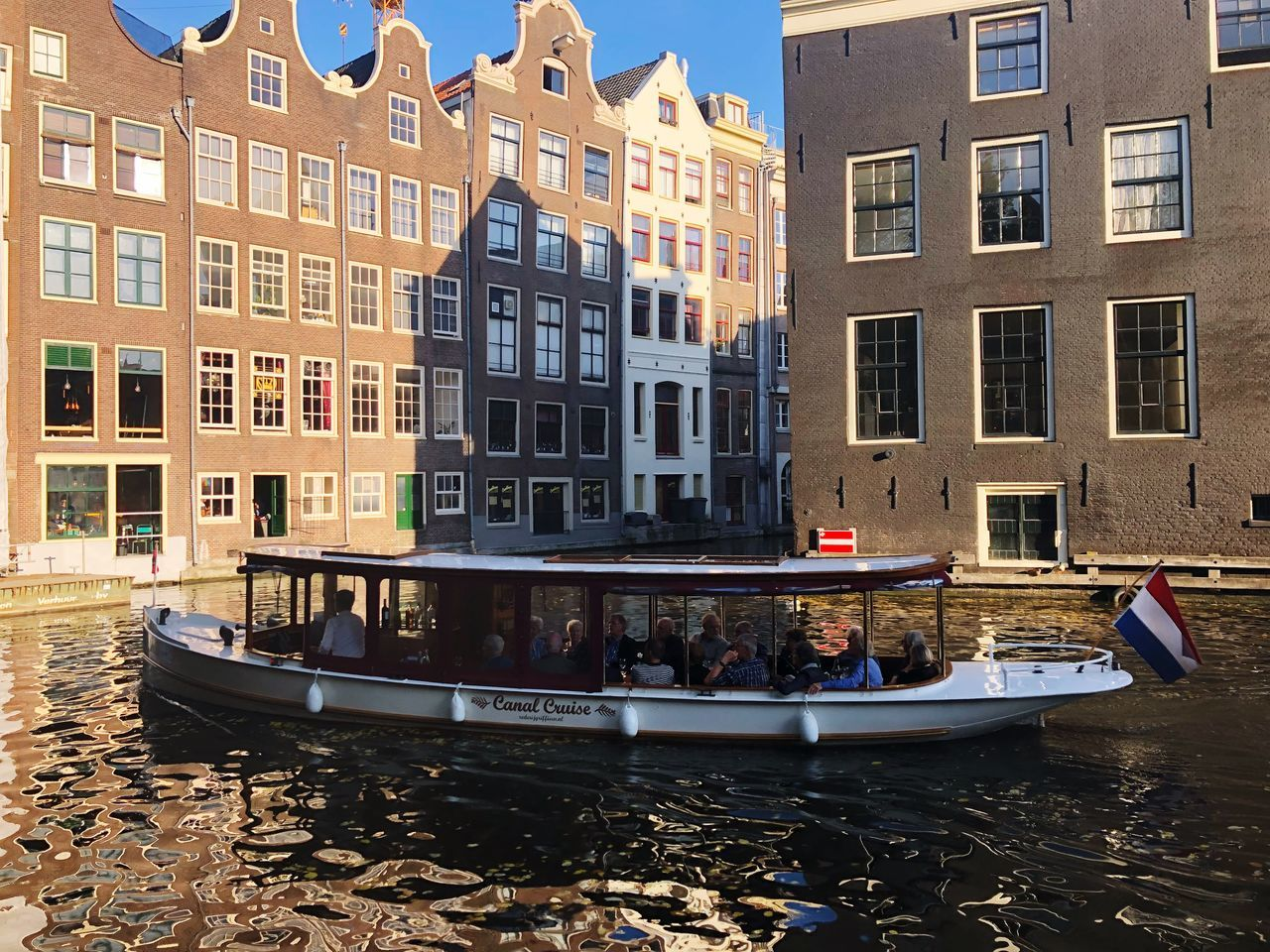 building exterior, built structure, architecture, nautical vessel, water, mode of transportation, transportation, canal, day, building, waterfront, city, moored, nature, window, travel, residential district, men, outdoors, passenger craft, row house