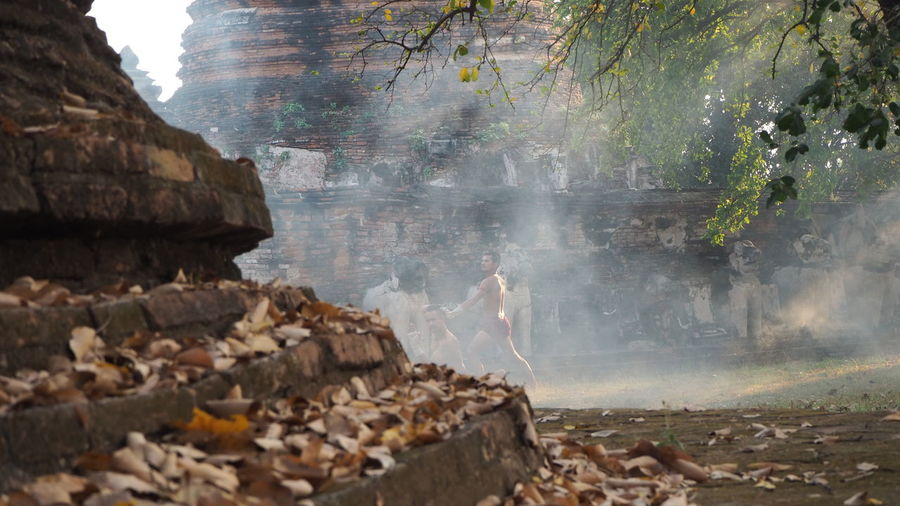 Shirtless men in smoke against old weathered temple at forest
