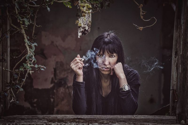 Portrait of serious woman smoking while leaning on abandoned house window