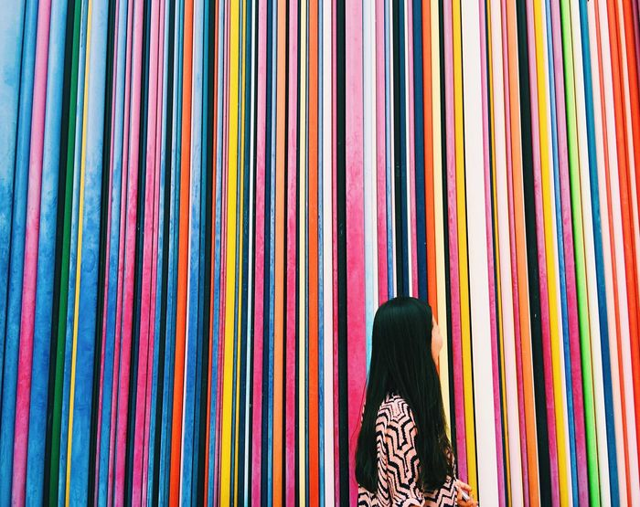 Side view of woman against colorful stripped wall
