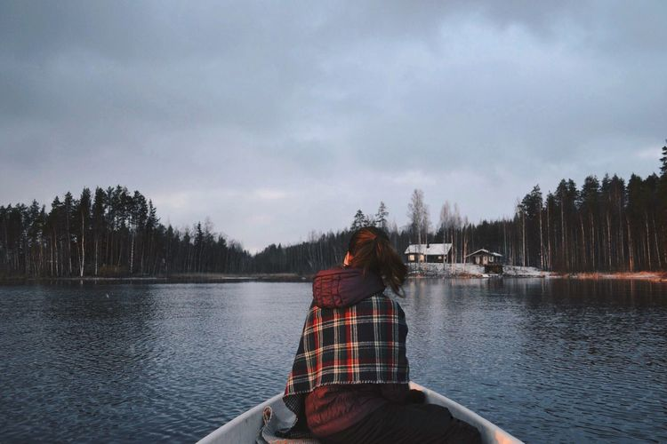 Rear view of woman sitting on boat against sky