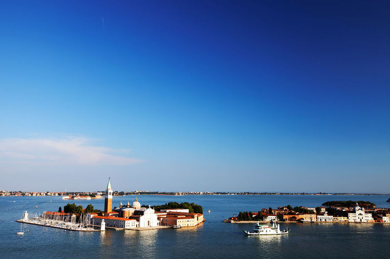 Mid distance view of san giorgio maggiore in grand canal against blue sky