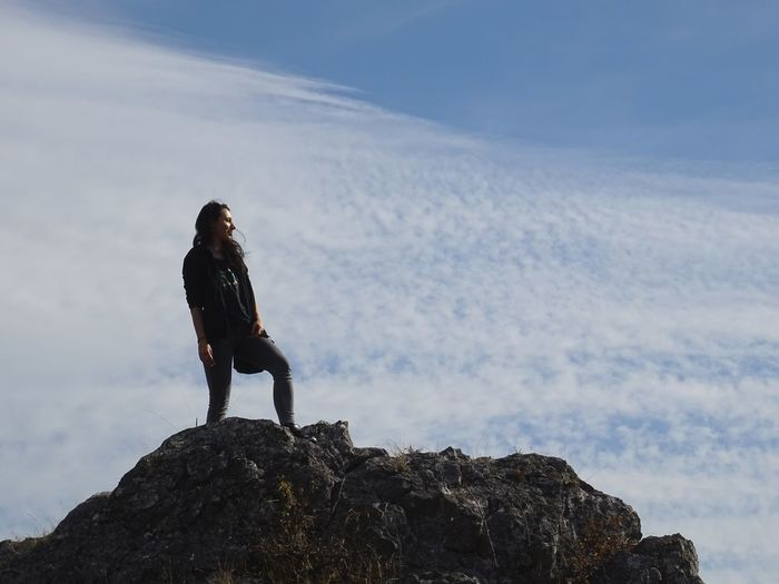 Low angle view of woman standing on rock against cloudy sky