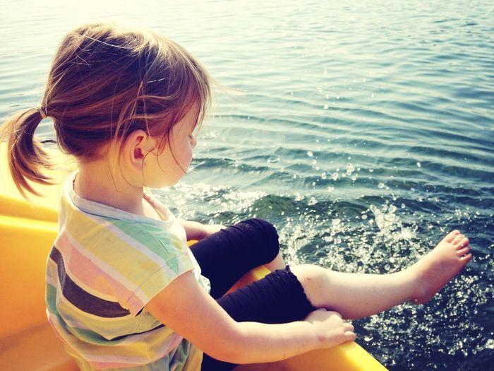 Full length of girl sitting in boat while splashing water