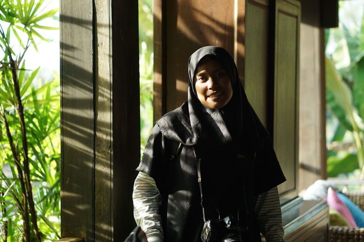 Portrait of smiling woman in hijab by window