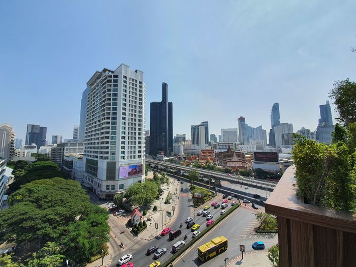 Panoramic view of city street and buildings against sky