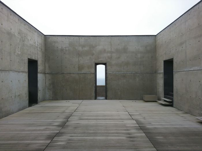 Roofless room with heavy thick concrete walls and three doors in symmetrical composition