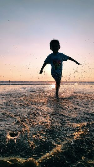 Full length of boy jumping in sea against sky during sunset