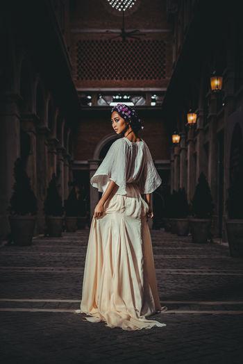 Full Length Portrait Of Woman Standing In Corridor