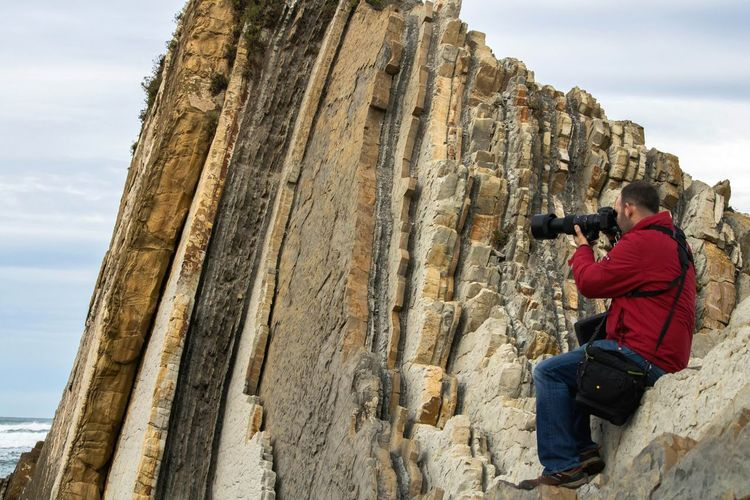 Low Angle View Of Man Photographing While Sitting On Rock Formations