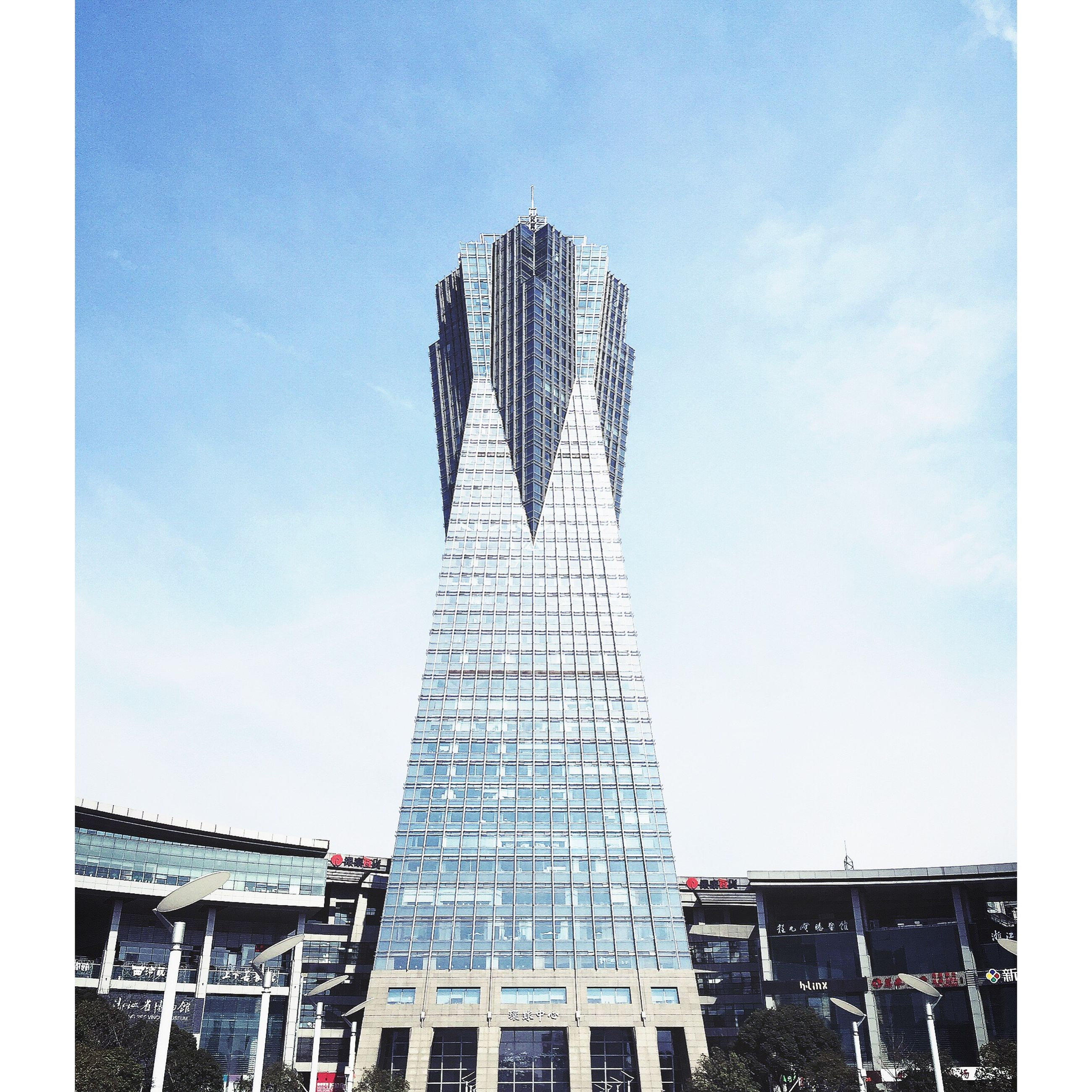 low angle view, built structure, architecture, building exterior, tall - high, sky, tower, modern, blue, city, day, building, outdoors, office building, skyscraper, tall, clear sky, development, auto post production filter, construction site