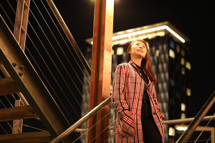 Low angle view of young woman looking away outdoors in the city nightlife