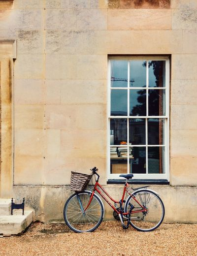 Bicycle parked against wall of house