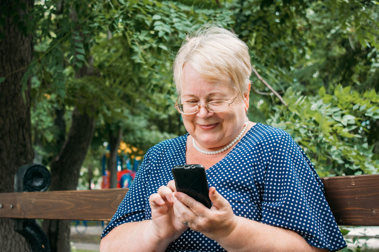 Mid adult woman using mobile phone outdoors