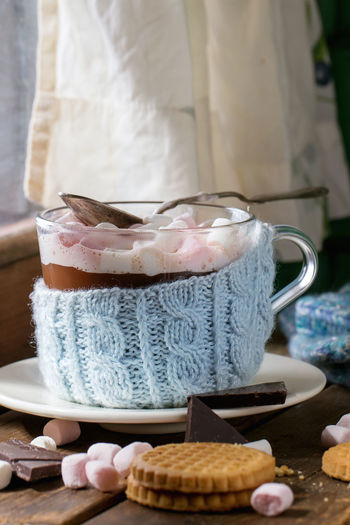 Glass cup of Hot chocolate with marshmallows in knitted cup holder with cookies, chopping chocolate and mittens over wooden window sill near frozen window in sunny day. Rustic style. Beverage Chocolate Coffee Dessert Marshmallow Pink Rustic Wintertime Drink Foam Food And Drink Foodphotography Glass Hot Chocolate Hot Drink Mug Sweet Sweet Food Table Window Window Sill