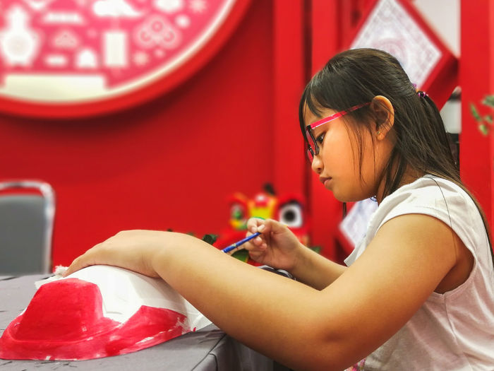 Little girl painting in conjunction of Chinese New year celebrations. Chinese New Year Chinese New Year 2019 Paint Painting Children Painting Asian Girl Young Girl Wearing Glasses Arts And Crafts Malay Red Background Holding Learning Hobby Red Women Indoors  Holding One Person Real People Females Child Girls Concentration Childhood Focus On Foreground Side View Lifestyles Children Pretty