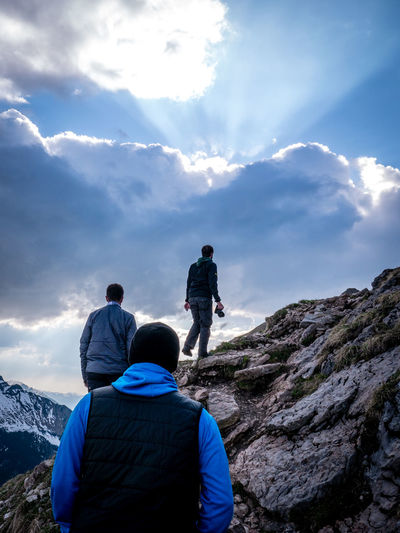 Rear view of men on mountain against sky