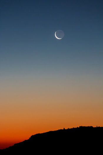 Sliver Moon Earthshine Orange Transitional Moments Astronomy Beauty In Nature Blue Crescent Idyllic Landscape Layers Moon Nature Scenics - Nature Sky Space Sunrise