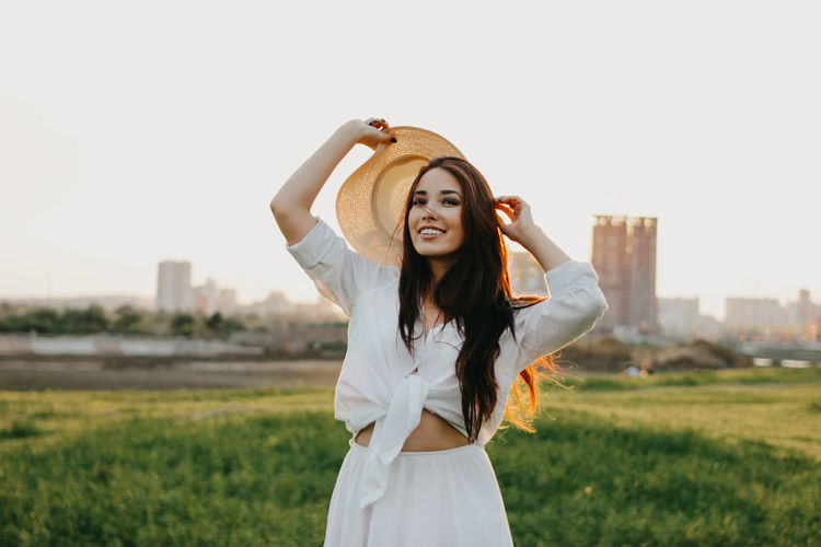 Portrait of beautiful young woman standing on land against sky