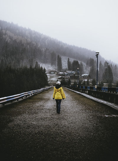 Rear view of woman walking on road during foggy weather