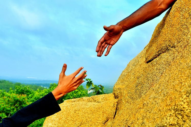 Cropped hand of man reaching towards woman hand against sky