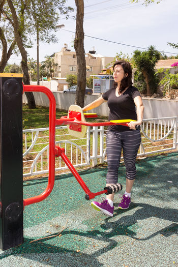 Woman in a sports simulator training on the playground outdoors Activities Athlete Athleticism Beautiful Building Clothing Cute Equipment Exercising Females Gym Hair Health Healthy Human Machine Muscular Person Practicing Simulator Smiling Sports Strength Trainer Training