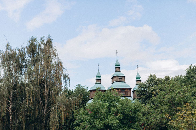 View of trees and building against sky
