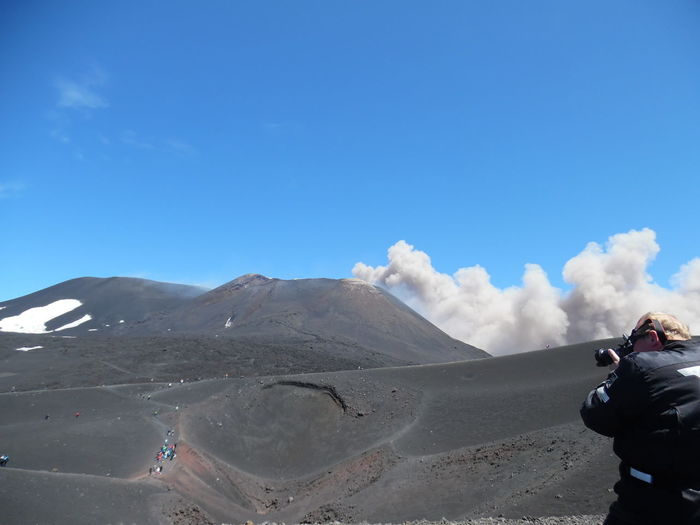 Man photographing etna volcano eruption with camera